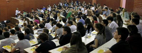 Varios jóvenes se enfrentan en una de las aulas de la Facultad de Biología de la Universitat de Barcelona a la primera jornada de las pruebas de selectividad